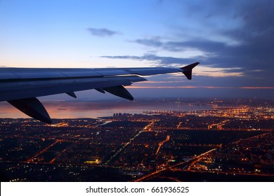 Wing view of civil passenger aiplane taking off at dusk with night city lights seen below.