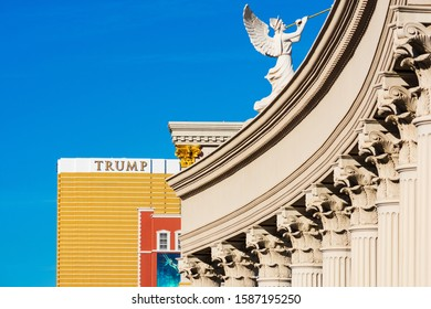 Winged angel blows trumpet atop columns at Caesars Palace hotel and casino. Trump International Hotel golden skyscraper in background - Las Vegas, Nevada, USA - December, 2019