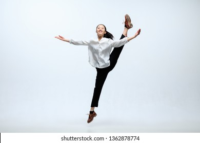 Winged flying by inspiration. Woman working at office, jumping and dancing in casual clothes or suit isolated on white studio background. Business, start-up, working open-space concept.