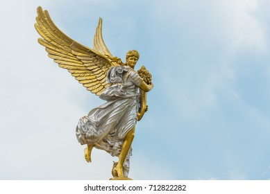 Winged gilded goddess in silver and gold holding cornucopia, a symbol of abundance and plenty.
