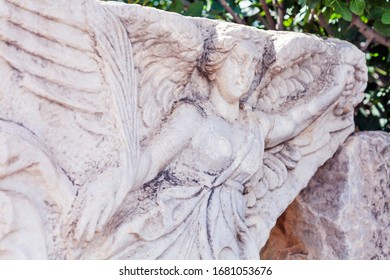 The Winged Goddess of Victory; Nike, at the ruins of the ancient city of Ephesus, Selcuk, Izmir, Turkey.  Nike is holding wreath and laurel leaves (bay leaves), in her hands. Ephesus is a UNESCO site.