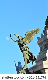 Winged Victory bronze statue at Vittoriano or Altar of the Fatherland from Piazza Venezia with the moon, Rome, Italy