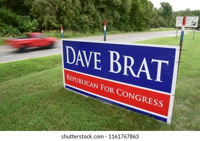 Wingmead, Virginia/USA - August 18, 2018: A red pickup truck drives by a campaign sign for Republican U.S. Rep. Dave Brat of Virginia.
