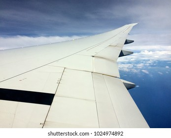 Wingtip of Boeing B777 in flight during cloudy day.
