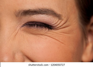 wink female eye with wrinkles around