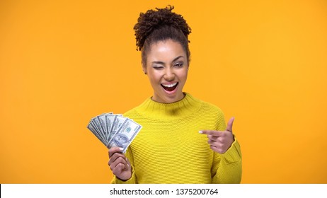 Winking female pointing at dollar bills, bank deposit, successful investment