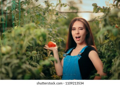 Winking Happy Farmer Woman Holding a Homegrown Tomato.Female entrepreneur growing organic vegetables