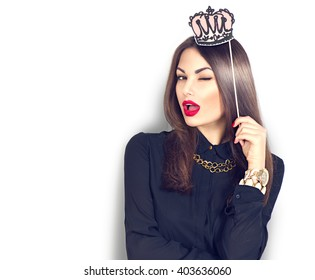 Winking sexy model Girl holding funny paper crown on stick isolated on white background. Joyful young fashion woman with bright make up, red lips and nails