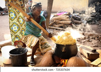 WINNEBA - GHANA - JULY 28, 2017: Unidentified woman prepares traditional corn porridge on July 28, 2017 in Winneba, Ghana