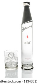 Winneconne, WI - 14 July 2018: A bottle of Stolihnaya elit vodka with a glass of ice on an isolated background.