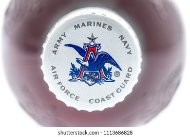 Winneconne, WI - 15 June 2018: A bottle cap with Anheuser Busch symbol with the armed forces around it on an isolated background.