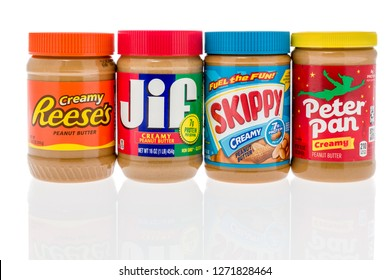 Winneconne, WI - 30 December 2018: A collection of peanut butter brands including Reeses, Jif, Skippy, and Peter Pan on an isolated background.