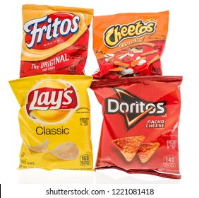 Winneconne, WI - 4 November 2018: Four bags of Frito Lay chips including classic potato, Doritos nacho cheese, cheetos crunchy and Fritos original corn chips on an isolated background.