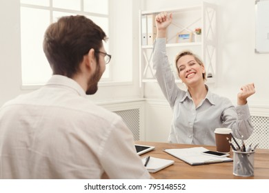 Winner business partners happy, successful, in white modern office, sitting at workplace. Happy businesswoman raised arms