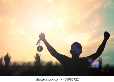 Winner concept: Silhouette champion hand holding gold medal reward against blurred sport stadium autumn sunset background