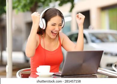 Winner girl euphoric watching a laptop in a coffee shop wearing a red shirt