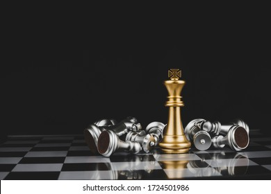 Winner. gold king surrounded with silver chess pieces on chess board game competition with copy space on dark background, chess battle, success, team leader, teamwork and business strategy concept