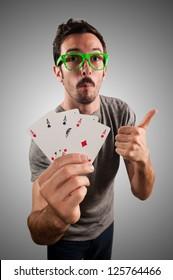 winner guy holding poker cards on grey background