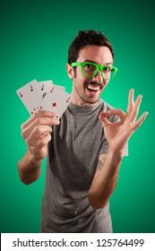 winner guy holding poker cards on green background