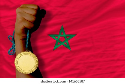 Winner holding gold medal for sport and national flag of morocco