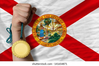 Winner holding gold medal for sport and flag of us state of florida