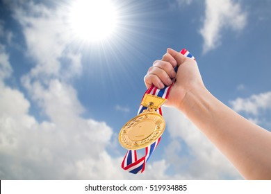 The winner holding golden medal to the sky for show team success with their business.