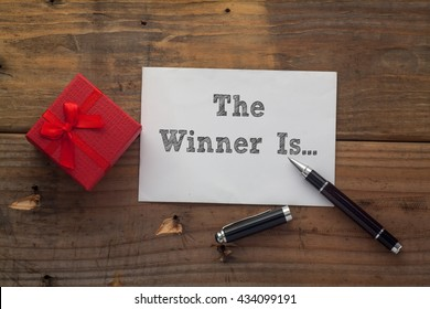The Winner Is... written on paper with pen,red gift box and wooden background desk.
