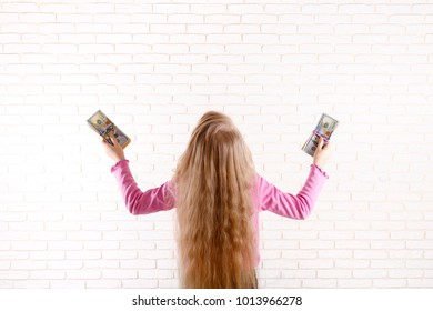 The winner is lucky girl with dollars in hands. The child won the lottery. A happy teenager stands back with money in his hands raised up on background of a light brick wall.