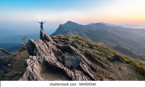 Winner man on peak of rocks mountain backpack at sunset