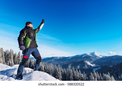 Winner standing with raised hand on a hill covered with snow, against winter mountain landscape