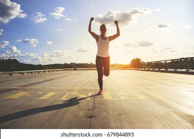 Winner as style of life. Horizontal shot of young beautiful woman in sports clothing keeping arms raised and smiling while passing finish line during jogging. Evening sunlight on background.