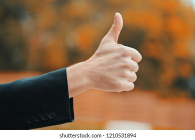 Winner. Success. Hand of man in business clothing gives thumbs up. Guy showing gesture of approval.