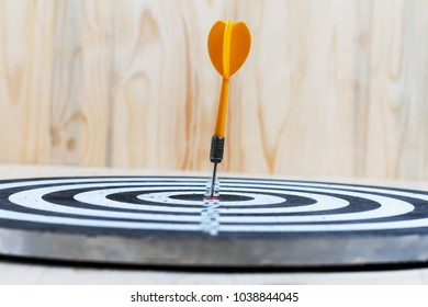 Winner Yellow dart arrow hit the center target of dartboard metaphor marketing competition concept, on wood background