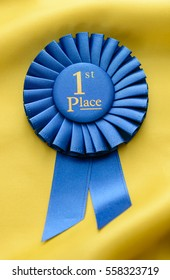 Winners 1st place championship rosette with pleated blue ribbon on gold fabric in a conceptual image of success and achievement