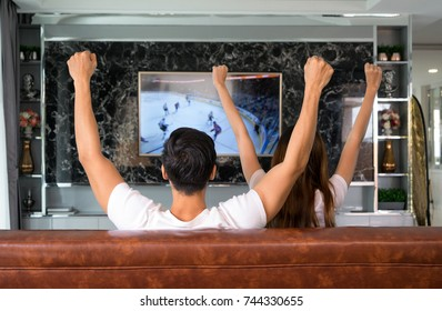 Winners! Friends are fans of sports games as football, basketball, hockey, baseball, love spending their free time at home together and happy. They are screaming and gesturing for a victory