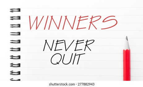 Winners Never Quit Text written on notebook page, red pencil on the right. Motivational Concept image