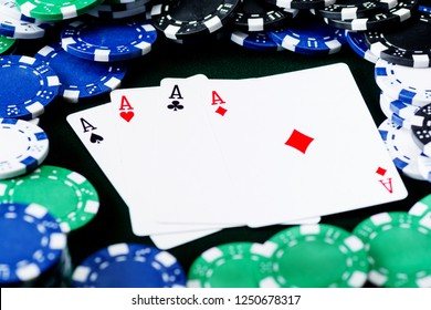 A winning poker hand of four aces playing cards suits on black background with poker chips