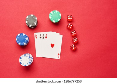 A winning poker hand of four aces playing cards suits on red background with chips and dices