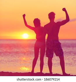 Winning success concept - happy beach couple at sunset with arms raised up outstretched cheering and happy. Beautiful young fitness couple, man and woman.
