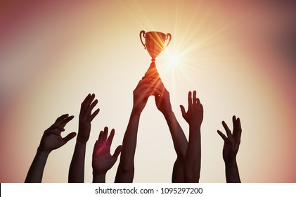 获胜的队伍手中拿着奖杯。 许多手在日落的轮廓.
