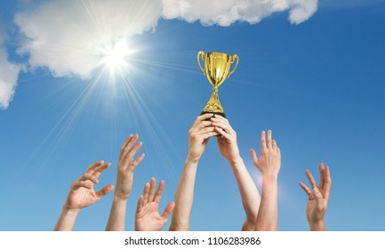Winning team is holding trophy in hands. Many hands against blue sky.