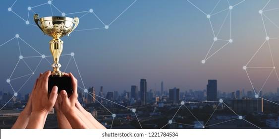 Winning team raise trophy cup with digital background, digital achievement conceptual