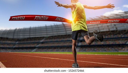 Winning young male Athlete crosses the finish line.