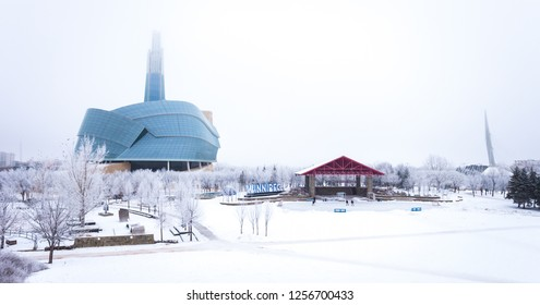 Winnipeg, Canada - December 2018: Winter scene at the Forks National Historic Site: frost covered trees, people skating on an outdoor rink, with the Canadian Museum for Human Rights in the background