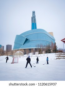 Winnipeg, Manitoba, Canada - December 2013: Family enjoying various winter activities (ice skating, ice hockey) at the Forks outdoor skate path. Background is the Canadian Museum of Human Rights.