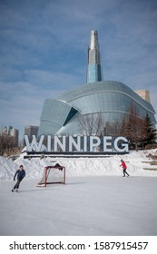 Winnipeg Manitoba / Canada - February 23rd 2019 : Two men are skating around the CN Stage at the Forks historic site near the famous Winnipeg sign and Canadian museum for human rights building