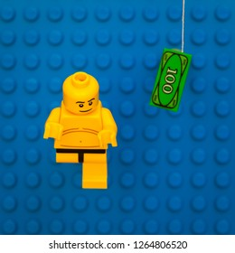 """Winnipeg, Manitoba / Canada - January 2012: A LEGO minifigure recreates the cover of the Nirvana album, """"Nevermind"""", which had a naked baby floating on a pool being lured by a paper bill"""