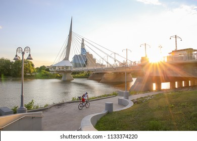 Winnipeg, Manitoba / Canada - July 10, 2018: Cyclists along Red River in a sunny day. Peaceful sunset scene