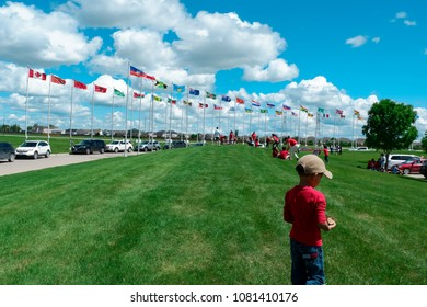 Winnipeg Manitoba Canada. July 1st 2017. The little boy was going to play around and walking in green lawn at Canada and international flage row. Celebration of Canada's day at Canada's Mint.
