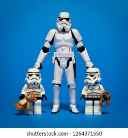 Winnipeg, Manitoba / Canada - November 2012: A Stormtrooper from Star Wars standing with his two Stormtrooper kids. Blue background